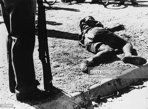 An armed man stands beside the body of one of the sixtynine black South Africans killed by police in the massacre at Sharpeville South Africa March...
