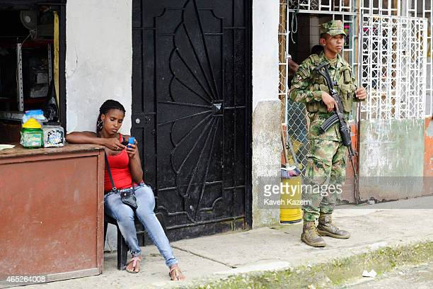 BUENAVENTURA COLOMBIA JANUARY 15 2015 An armed marine from the navy infantry stands next to a woman busy with her mobile phones on the street near...