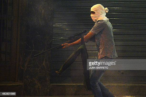 An armed masked and unidentified man runs during a protest against Venezuelan President Nicolas Maduro in Caracas on April 4 2014 Protests broke out...