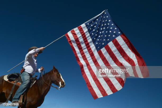 An armed member of a group calling themselves 'Cowboys for Trump' prepares to lead a group of other horsemounted Donald Trump supporters through the...