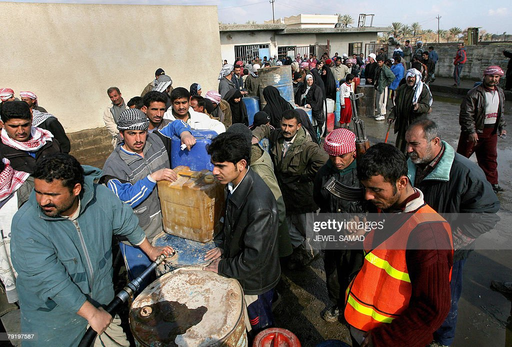 An armed member of the Concerned Local Citizens (CLC), an anti Al-Qaeda group, stands guard (R) as Iraqis queue up to fill their jerrycans with gasoline in southern Baghdad, 24 January 2008. A suicide bomber disguised as a policeman killed the provincial police chief for Iraq's main northern city of Mosul today as he visited the scene of an earlier blast in which 34 people died, police said. AFP PHOTO/Jewel SAMAD