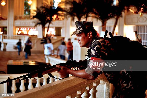 An armed member of the Magdalo group stands guard for Senator Antonio Trillanes and General Danilo Lim inside the Peninsula Hotel in the business...