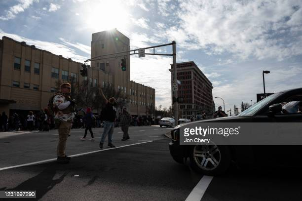 An armed member of the militia known as the Boogaloo Bois blocks traffic so protesters can pass during a Breonna Taylor memorial march near Jefferson...