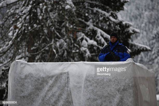 An armed member of the Swiss Police stands on duty at a security checkpoint outside the Congress Center venue for the World Economic Forum in Davos,...