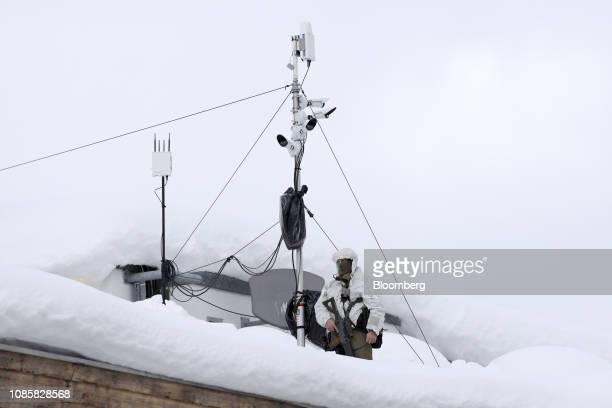 An armed member of the Swiss Police watches from the Congress Center rooftop ahead of the World Economic Forum in Davos Switzerland on Monday Jan 21...