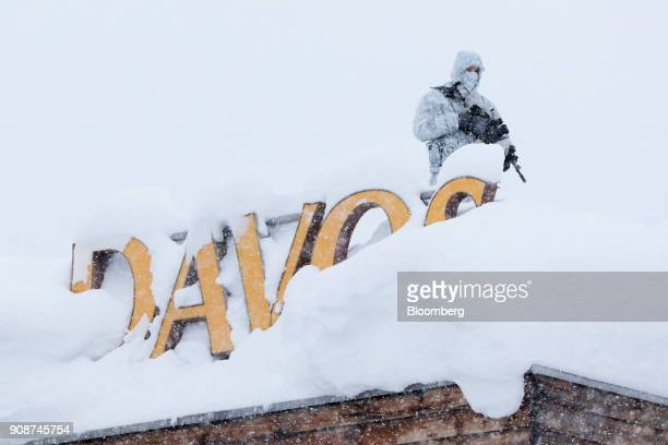 An armed member of the Swiss Police watches from the roof of the Hotel Davos ahead of the World Economic Forum in Davos Switzerland on Monday Jan 22...
