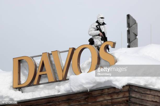 An armed member of the Swiss police watches from the snowcovered roof of the Hotel Davos on day three of the World Economic Forum in Davos...