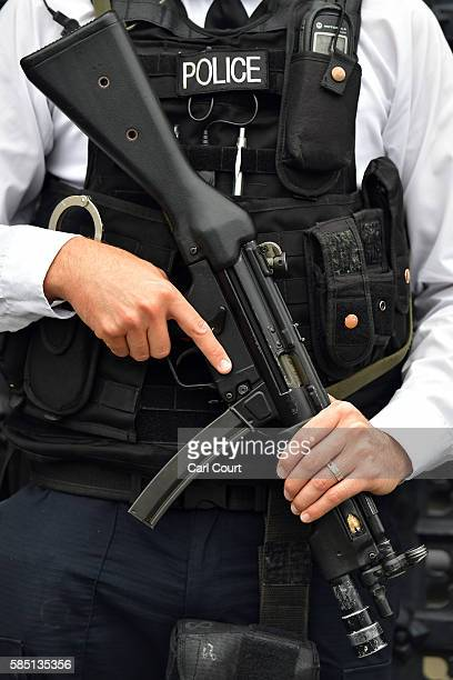 An armed Metropolitan Police officer patrols outside the Houses of Parliament on August 2 2016 in London England Security measures continue to be...