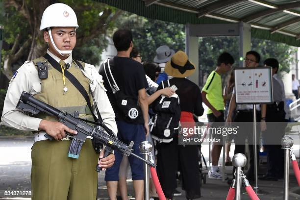 An armed military police keeps watch at an entrance for public visitors to the Presidential Palace complex in Taipei on August 18 2017 A samurai...