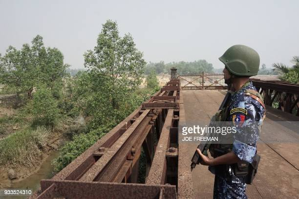 An armed Myanmar borderguard police is posted at the Friendship Bridge across Bangladesh located in Maungdaw district in Rakhine State on March 18...