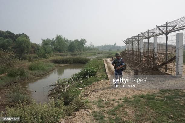 An armed Myanmar borderguard police patrols the barbed wire border fence along Bangladesh in Maungdaw district in Rakhine State on March 18 2018...