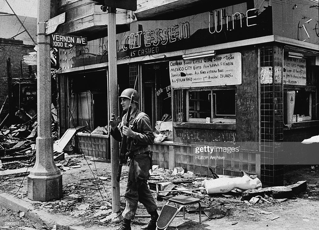 An armed National Guard patrolman leans against a street sign, smoking a cigarette and standing in rubble following the Watts riots, Los Angeles, California, August 1965.
