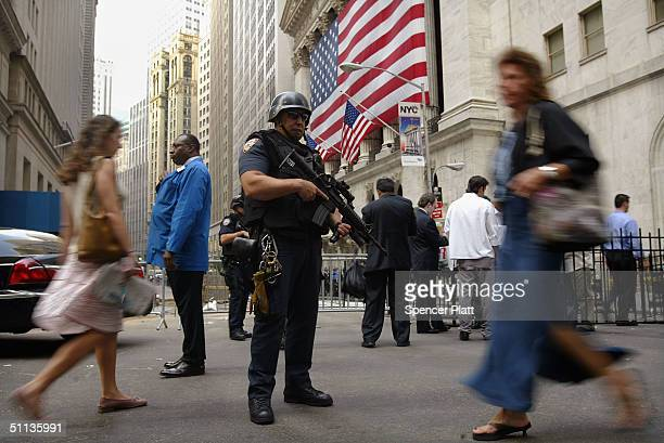 An armed NYPD officer guards the New York Stock Exchange August 2 2004 in New York City The US federal government raised the terror alert to orange...