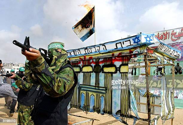 An armed Palestinian from the military wing of the militant group Hamas performs a mock attack on a model of the Israeli Knesset building while an...