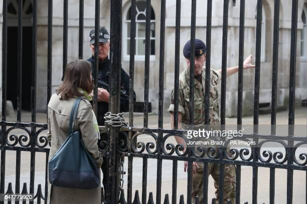 An armed police officer and soldier behind locked gates at the entrance to Horse Guards in Whitehall central London as Operation Temperer is enacted...