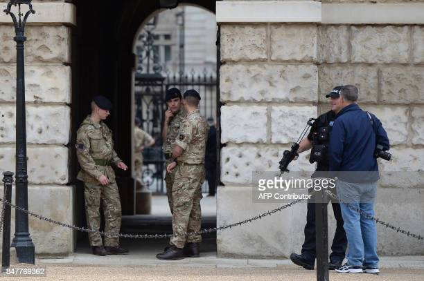 An armed police officer and three military personel stand guard outside the Horse Guards Parade in central London on September 16 2017 British police...