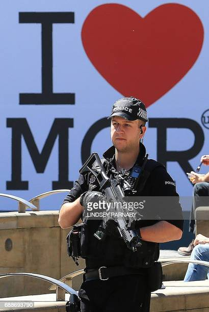 An armed police officer carries his weapon as he passes an I Love MCR symbol in Manchester northwest England on May 26 2017 Britain is hunting for a...