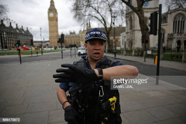 An armed police officer gestures as he stands guard in Parliament Square opposite the Houses of Parliament in central London on March 22 2017 during...