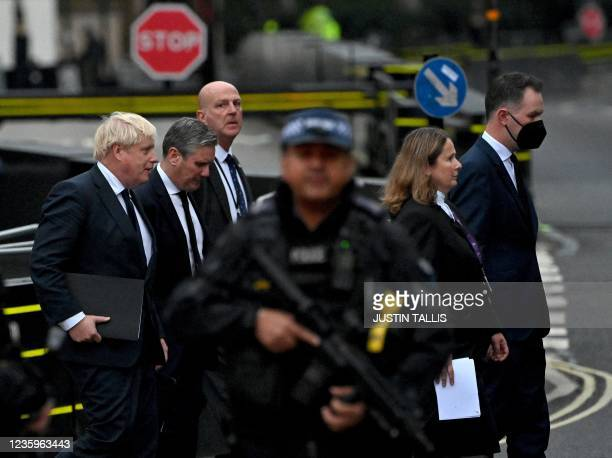 An armed police officer holds his gun as Britain's Prime Minister Boris Johnson and Britain's main opposition Labour Party leader Keir Starmer lead...