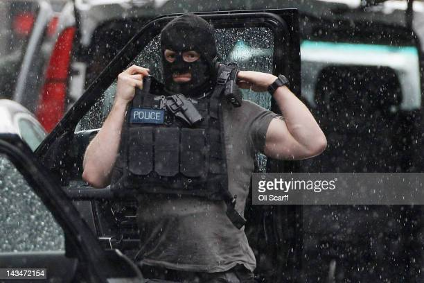 An armed police officer in Tottenham Court Road prepares himself during a suspected hostage situation on April 27 2012 in London England The busy...