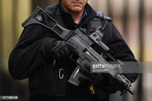 An armed police officer is seen in Downing Street in central London on December 12, 2018. - British Prime Minister Theresa May was hit by a...