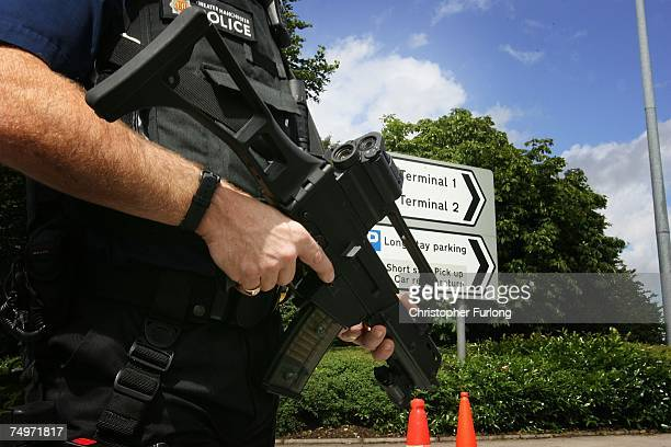 An armed police officer observes vehicles at a check point at the entrance to Terminal 3 of Manchester Airport on July 1, 2007 In London, England....