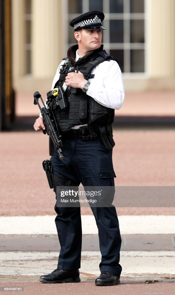 An armed police officer on duty outside Buckingham Palace during The Colonel's Review on June 10, 2017 in London, England. The Colonel's Review is the second rehearsal for Trooping the Colour, the ceremonial event marking the official birthday of Queen Elizabeth II.