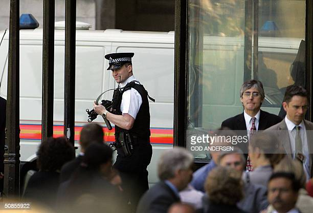 An armed police officer oversees the evacuation of the House of Commons in London, 19 May, 2004 when the British parliament was suspended and...