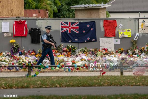An armed police officer passes flowers and tributes near Al Noor mosque on March 22 2019 in Christchurch New Zealand 50 people were killed and dozens...