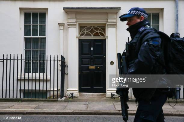 An armed police officer passes number 11 Downing Street ahead of Rishi Sunak, U.K. Chancellor of the exchequer, presenting his budget statement in...