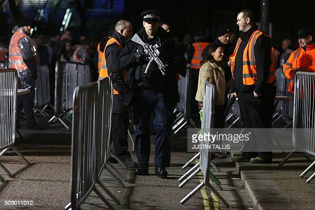An armed police officer patrols at a security bagsearch area where spectators are queueing to enter the area to watch the New Year's Eve fireworks in...