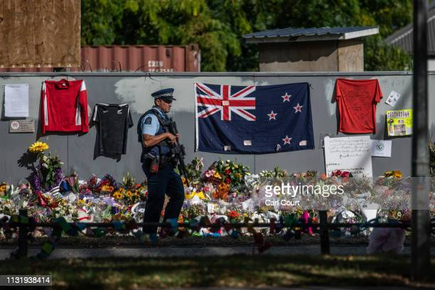 An armed police officer patrols past a New Zealand flag and other tributes near Al Noor mosque, on March 22, 2019 in Christchurch, New Zealand. 50...