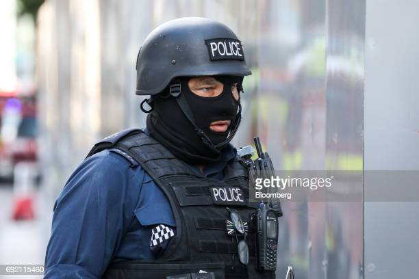 An armed police officer patrols streets near the scene of a terror attack in London UK on Sunday June 4 2017A van swerved into Saturdaynight crowds...