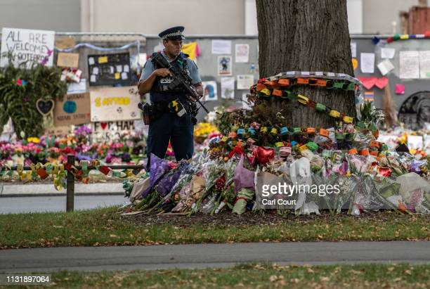 An armed police officer pauses by flowers and tributes outside Al Noor mosque on March 22 2019 in Christchurch New Zealand 50 people were killed and...