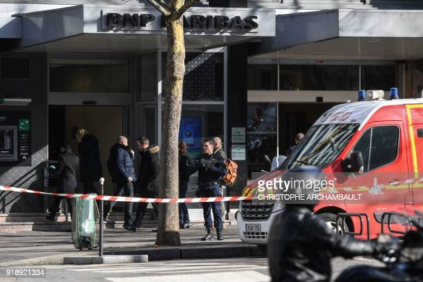 An armed police officer secures the cordonedoff area next to a rescuers van and investigating officers following a bank robbery attempt in a branch...