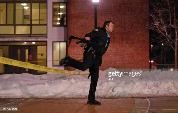 An armed police officer secures the Northern Illinois University campus following a deadly shooting that killed four students and injured 14 others...