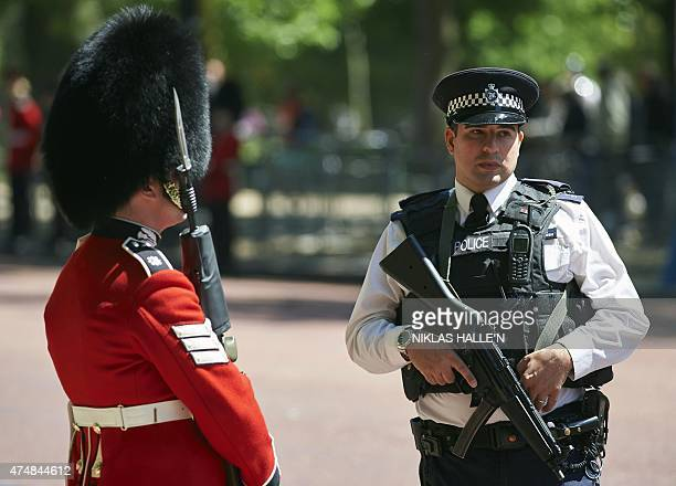 An armed police officer stands alongside a guardsman as Britain's Queen Elizabeth II travels along the Mall to the Palace of Westminster in central...