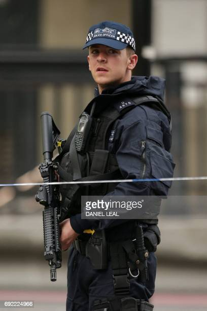An armed police officer stands at a police cordon at the north end of London Bridge in London on June 4 as police continue their investigation...