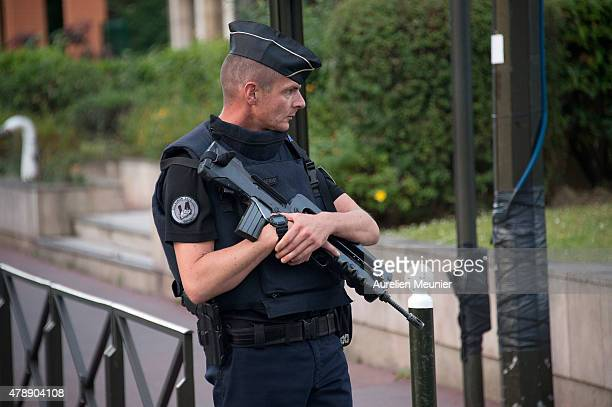 An armed police officer stands guard as police cars cars believed to be carrying the suspect of Friday's attack on the USowned Air Products and...