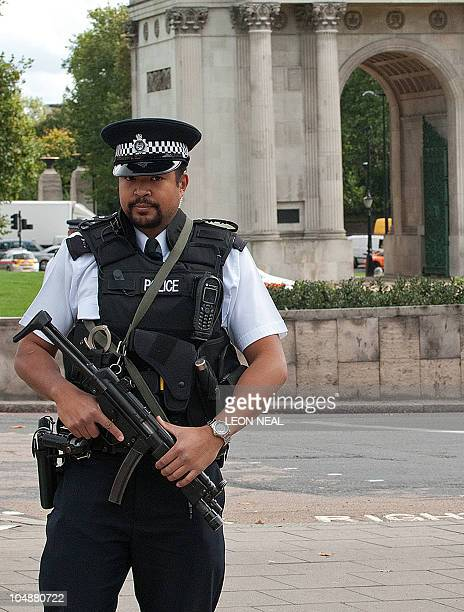 An armed police officer stands guard as the area aound Hyde Park Corner is evacuated during a security alert in central London on October 6 2010 The...