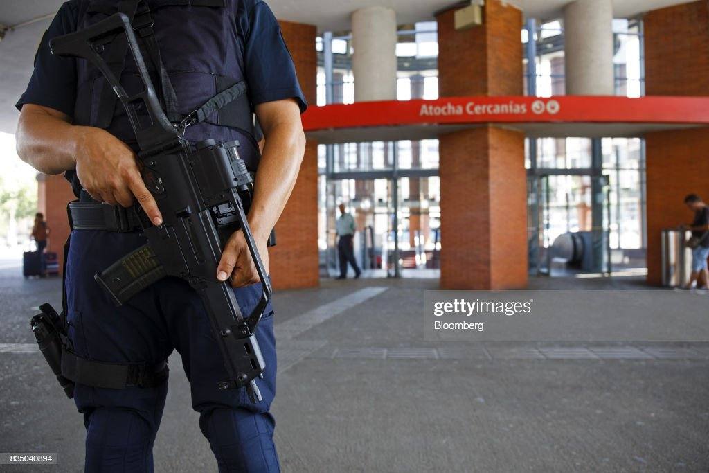 An armed police officer stands guard at the entrance to Atocha railway station in Madrid, Spain, on Friday, Aug. 18, 2017. Terrorists behind the Barcelona attack had planned a devastating assault with explosives and may have rammed pedestrians with vehicles after their initial plan failed, the police chief heading the investigation said on Friday. Photographer: Angel Navarrete/Bloomberg via Getty Images
