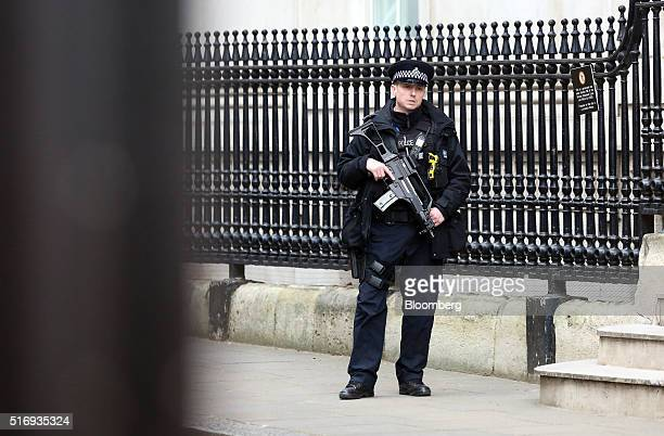 An armed police officer stands guard in Downing Street in London UK on Tuesday March 22 2016 Explosions ripped through the Brussels airport departure...