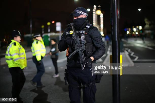 An armed police officer stands guard on Westminster Bridge as thousands gather to ring in later tonight the New Year on December 31 2017 in London...