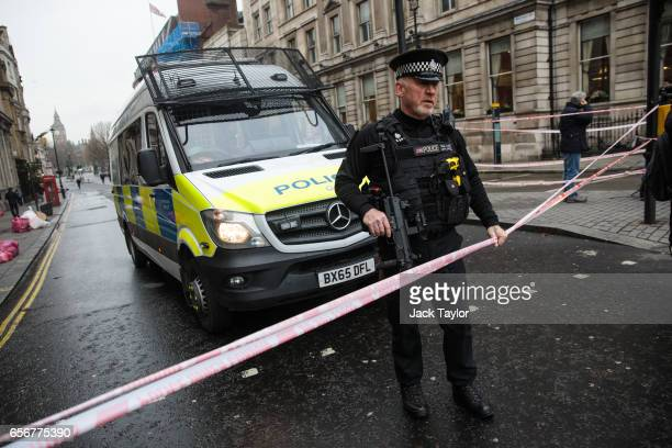An armed police officer stands guard on Whitehall following yesterday's attack on March 23 2017 in London England Four people have been killed and...