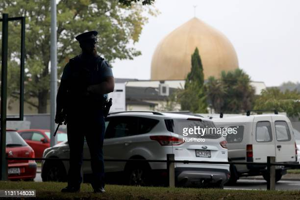 An armed police officer stands guard outside the Al Noor mosque in Christchurch New Zealand on March 17 2019 At least 50 people were killed and 36...