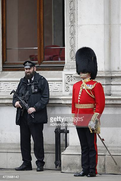An armed police officer stands next to a guardsman during the VE Day service of remembrance at the Cenotaph on Whitehall in London on May 8 to...