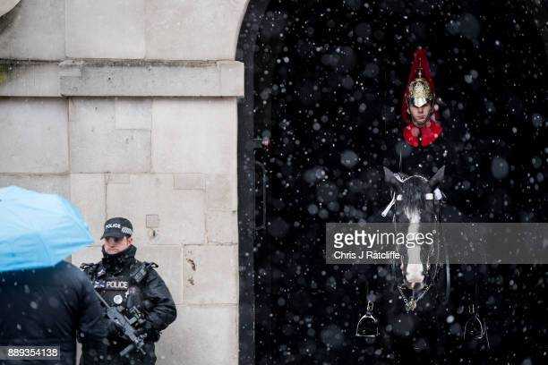 An armed police officer stands next to a member of the Household Cavalry on guard at Horse Guard's Parade as snow falls briefly on the British...