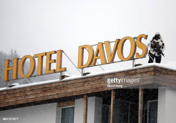 An armed police officer stands on the snowcovered rooftop of the Hotel Davos and looks out over the Congress Center the venue for the World Economic...