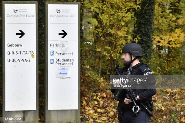 An armed police officer stands outside The Drie Eiken Campus of The University of Antwerp, in Antwerp on November 25 after unknown person launched a...