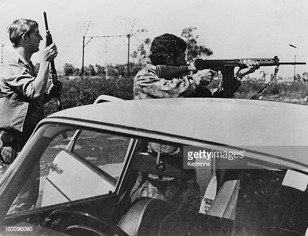 An armed police officer trains his rifle on demonstrators during unrest near Cape Town South Africa 16th September 1976 The violence comes in the...